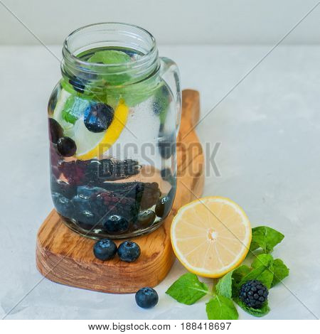 Infused Detox Water With Lemon Blackberry Blueberry And Mint Leaves In A Mason Jar