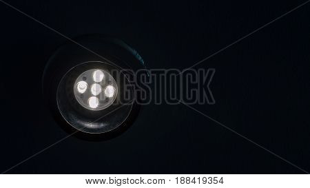 Energy saving led spotlight with flare up in the ceiling in the dark with copy space