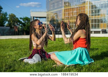 Two girl friends with zizi cornrows dreadlocks giving high five to each other. Happy moment. Pure emotions