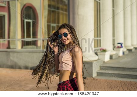 Young beautiful girl with zizi cornrows dreadlocks corrects her hair on the street. Urban city style. She is happy smiling and looking at camera.