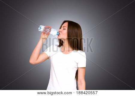 Happy attractive girl standing over gray background and looking at camera. With a bottle of clean drinking water in hand
