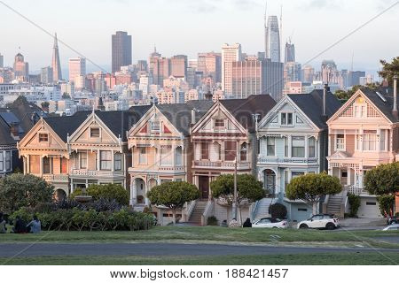 Sunset Over The Painted Ladies. Iconic Victorian Houses and San Francisco Skyline in Alamo Square, San Francisco, California, USA.