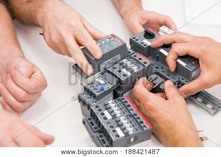 electricians' hands holding a residual current device