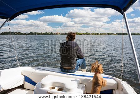 Man with his dog in motor boat on the river. Summer vacation yacht sailing, water sport. Yachtsman traveling by motorboat, unrecognizable person, sunny summer outdoor on blue cloudy sky background.