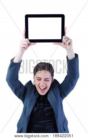 Photo of celebrating young business woman standing over white background showing display of tablet computer ander her head. Focus on her eyes.