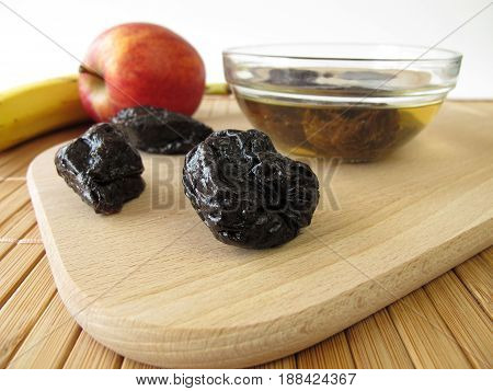 Dried plums an other fruits on wooden board