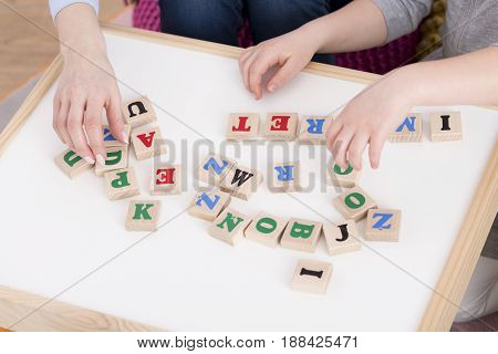 Wooden blocks with letters on white board using in education