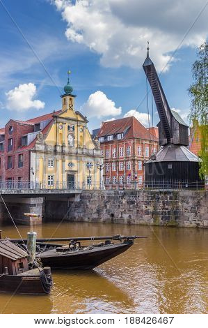LUNEBURG, GERMANY - MAY 21, 2017: Old wooden crane and colorful historic buildings in the harbor of Luneburg