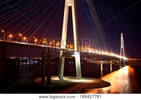 beautiful night city lights. high bridge across the Bay stretched on pylons. in water reflected glare from the bridge