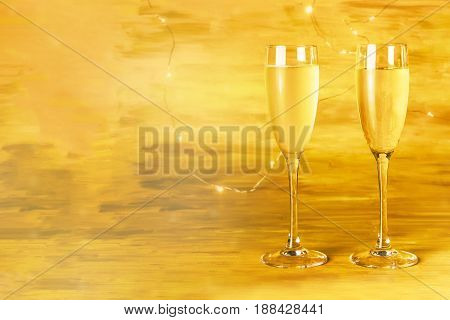 A side view of two glasses of champagne on a blurred golden background with a place for text