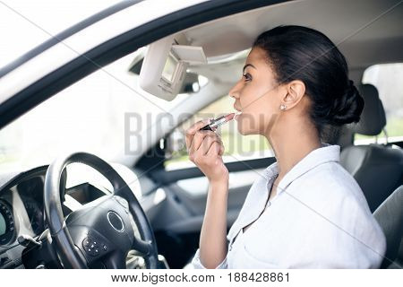 Side View Of Businesswoman Applying Lipstick On Lips In Car