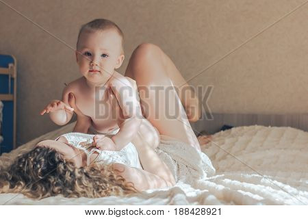 Portrait of mother and baby playing and smiling at home.