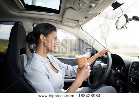 Side View Of Woman Driving Car With Coffee To Go In Hand