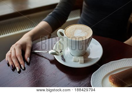 Cup Of Coffee With Foam And Tiramisu Cake On The Table