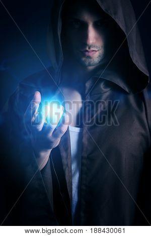 handsome wizard showing an energy blast on a dark background