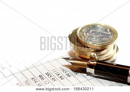 Closeup of coins stack on paper background with digits