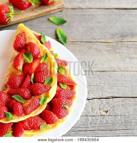 Summer berry omelette. Colorful easy omelette stuffed with fresh strawberries and garnished with mint on a plate and wooden background with empty copy space for text. Breakfast or lunch omelette idea