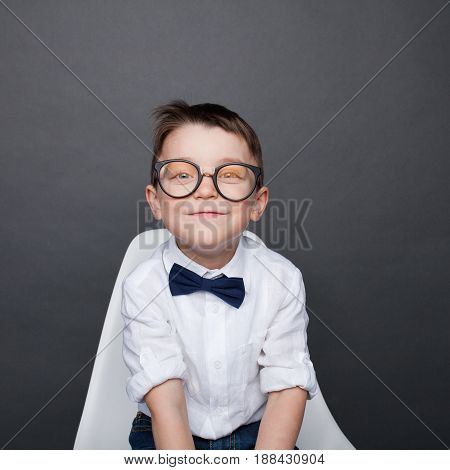 Small lovely boy in glasses wearing white shirt with bowtie smiling at camera on studio background.