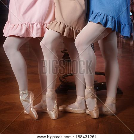 Young fashion ballerinas in colourful dresses doing the pas