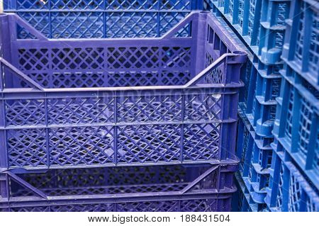 Close up pile of blue and violet plastic boxes outside