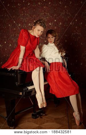 Young fashion caucasian ballerinas sitting on the piano and laughing