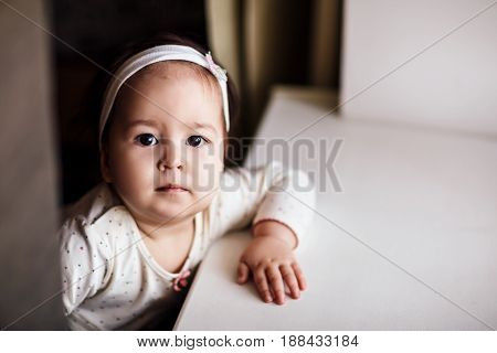 Charming and curious little girl looking at camera indoors.