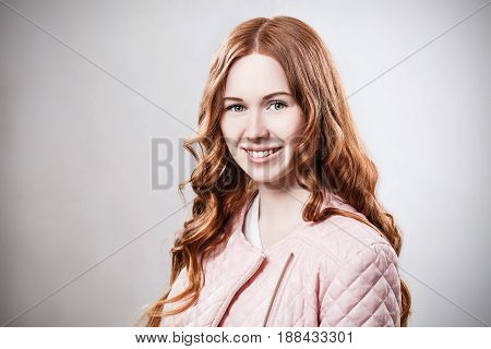 Portrait of smiling redhead girl in pink jacket over gray wall background.