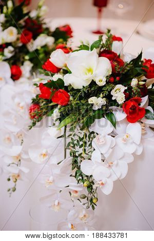 Gorgeous bouquet of white orchid and red roses on newlyweds table