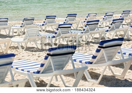 Lots of sun loungers on the beach near the sea. Selective focus.