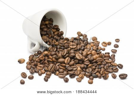 overturned coffee cup with bunch of coffee beans on white background
