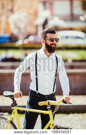 A young stylish businessman going to work by bike. hipster with a fixie bicycle on the street. bearded man looking away while riding on his bicycle outdoors poster