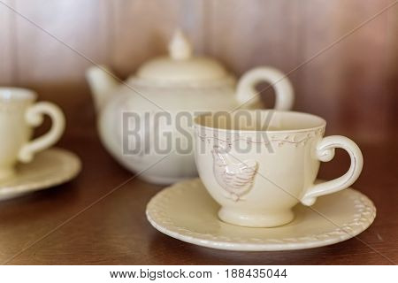 Teapot and cups with image of chicken on them are prepared for tea drinking in cafe