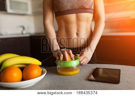 Unrecognizable woman standing in the kitchen and making fresh orange juice.