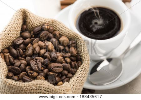cup of coffee on napkin with canvas bag full of coffee beans and cinnamon on white background