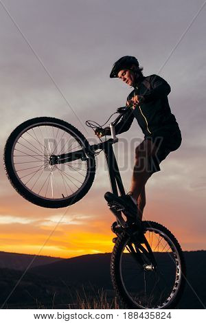Man in sportswear trick on bike on background of sunset in mountains