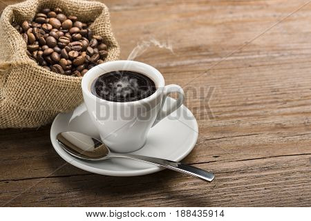 cup of coffee with canvas bag full of coffee beans on wooden table.