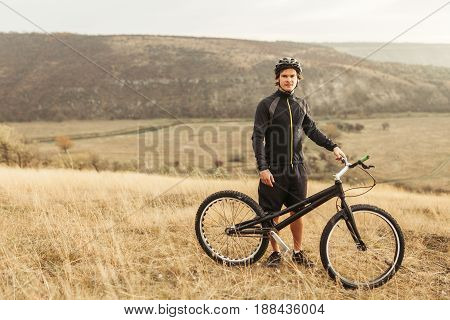 Young man in sportive outfit standing with mountain bicycle in field with mountains on background.