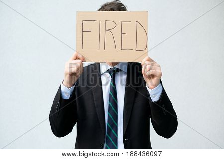 Fired businessman hiding his face with a message