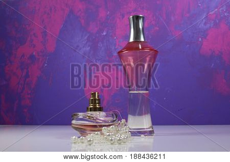 Two bottles of perfume on violet and pink background.
