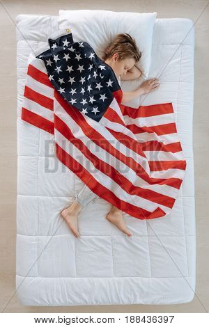 My homeland. Nice good looking pleasant boy being covered with the US flag and having patriotic dreams while being asleep