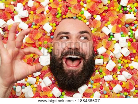 Young bearded man looking excitedly away while lying in sweets and holding marshmallow in hand.