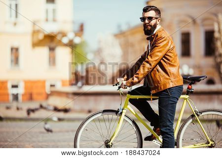 Side View Of Handsome Young Bearded Man In Sunglasses Looking Away While Riding On His Bicycle Outdo