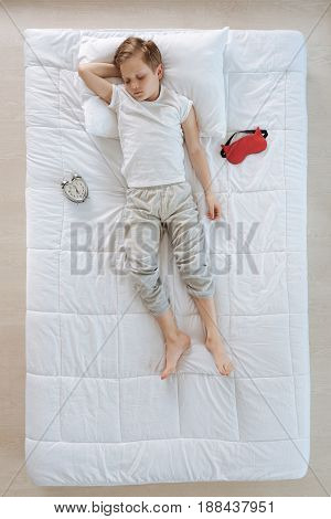 Peaceful sleep. Top view of a cute pleasant nice boy resting in his bed and having a peaceful sleep while being surrounded by a sleeping mask and an alarm clock