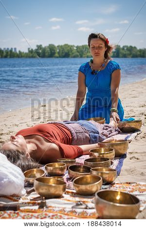 Young beautiful woman doing foot massage with tibetan singing bowls around in natureon the river bank