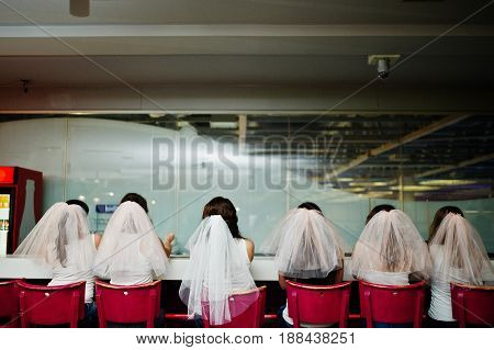 Back Of Six Girls On Veil Sit At The Bar Stools On Hen Party.