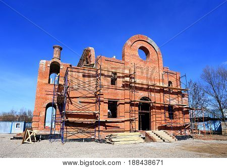 Erection of the red brick building with the scaffolding