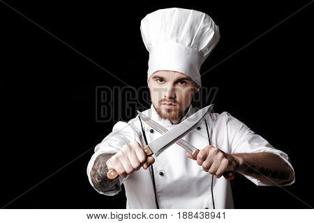Young bearded man chef In white uniform holds Two knives on a black background. Focus on knives