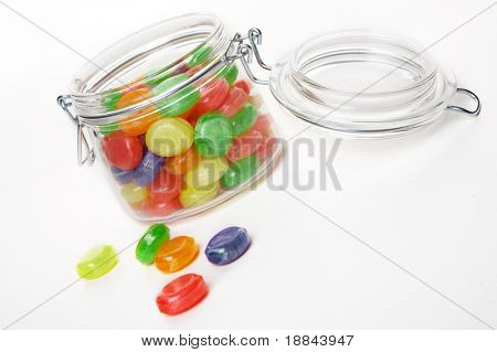 Colour sweets in a glass jar on a white background