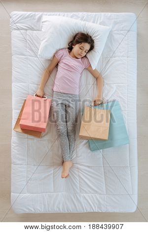 Shopping spree. Cute beautiful pleasant girl holding bags and shopping while being in her dream