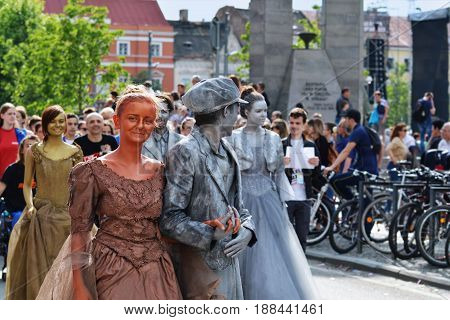 CLUJ-NAPOCA ROMANIA - MAY 27 2017: Young couples with golden and silver body painting and aristocratic dresses march on the streets at the opening parade of the Cluj Days festival